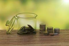 钱币及奖章收集家的概念在瓶金钱 免版税库存图片