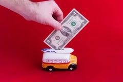 钱箱,以有两美元的衡量单位的一辆陶瓷公共汽车的形式,在红色背景 挽救的概念 图库摄影