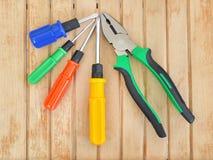 钳子和不同的大小四把螺丝刀与蓝色,绿色,红色和黄色把柄的在一张木桌上 免版税库存照片