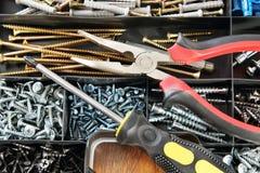 钳子和螺丝刀在有许多螺丝的一个塑料盒说谎 库存照片