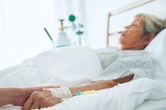 钻孔资深耐心` s手和安慰她的医生, 免版税库存图片