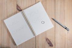 钻戒顶视图在白色笔记本的有信件`您与我结婚`和灰色铅笔在木桌上 库存照片