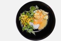 钾nom jeen,泰国米细面条服务用在白色隔绝的黑碗的咖喱 免版税库存图片