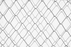 铁丝网和阴影在白色混凝土墙上 免版税库存图片