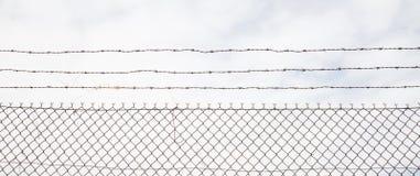铁丝网篱芭由钢制成有多云天空背景 关闭与细节的看法,横幅 图库摄影
