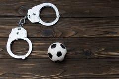 铁为罪犯的拘留,在木背景的一个足球扣上手铐 免版税库存照片