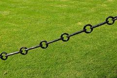 铁健壮的链子在草坪的 免版税图库摄影