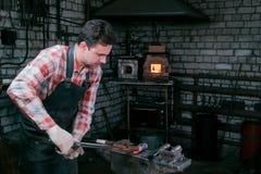 铁匠与新的轴一起使用炽热金属制件在铁砧的在伪造 供以人员纵向 免版税库存照片