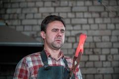 铁匠和铁砧 铁匠与新的锤子一起使用炽热金属在铁砧的在伪造 免版税库存图片