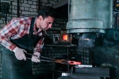 铁匠工作区  铁匠与在伪造的炽热金属一起使用 免版税图库摄影