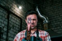 铁匠工作区  铁匠与新的锤子一起使用炽热金属制件在伪造的铁砧 看 库存照片
