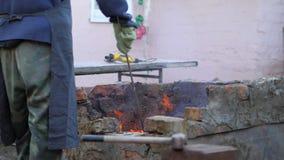 铁匠工作金属 工匠,私有铁匠铺的高地居民在村庄 工匠干涉炭烬 股票视频