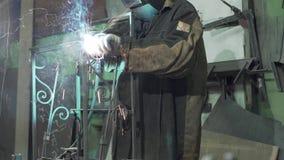 铁匠投入一件防护盔甲并且焊接联接 股票视频