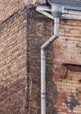 铁在砖墙上的雨天沟 免版税库存图片