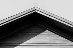 铁宽容十字架的单色图象在residentual房子屋顶的 免版税库存图片