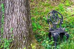 锻铁庭院椅子在森林 库存图片