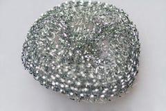 铁洗碗特写镜头谎言的金属海绵在灰色背景 免版税库存照片