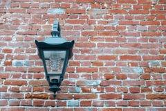 铁灯笼在一个老砖墙上垂悬 在灯现代灯被扭转 纹理 库存图片