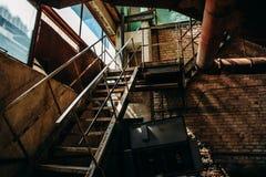 铁生锈的楼梯在被放弃的工厂的砖商店,在内部里面 免版税库存图片