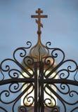 锻铁篱芭和一个十字架在白色石orthod圆顶  免版税库存图片