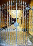 铁老加工的篱芭 在黄色大厦的伪造的华丽美好的样式变灰的门 库存图片