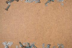 铁螺栓和坚果在纤维板 库存照片