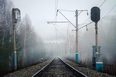 铁路、红灯和电杆看法在雾在春天 免版税库存照片
