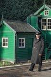 铁路卫兵步行通过了老信号房 免版税库存图片