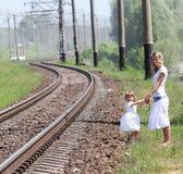 铁路和有她的女儿的一个母亲 库存图片