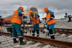 铁路工作者在雨中的修理路轨 库存照片