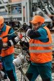 铁路工作者在雨中的修理路轨 图库摄影
