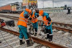 铁路工作者在雨中的修理路轨 免版税库存照片