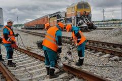 铁路工作者在雨中的修理路轨 免版税库存图片