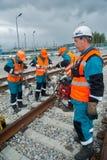 铁路工作者在雨中的修理路轨 免版税图库摄影