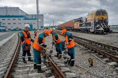 铁路工作者在雨中的修理路轨 库存图片
