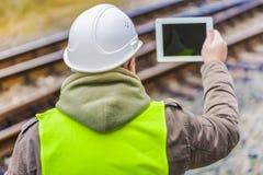 铁路工程师有片剂个人计算机的被摄制的路轨 库存图片