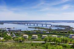 铁路河上的桥伏尔加河,海岸,大厦,石油产品的,近海处罐车储存箱,反对天空和clou 免版税库存照片