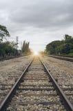 铁路的长度的看法与绿色树的在增加的铁路、被过滤的图象、光线影响和火光的左右边 免版税库存图片