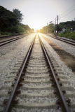 铁路的长度的看法与绿色树的在铁路的左右边,被过滤的图象,增加的光线影响 图库摄影
