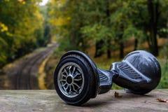 以铁路路轨为背景的黑hoverboard 库存图片