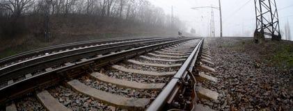铁路轨道在一个有薄雾的早晨 很多路轨和睡眠者 库存照片