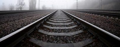 铁路轨道在一个有薄雾的早晨 很多路轨和睡眠者 免版税图库摄影