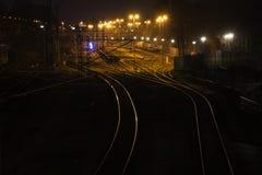 铁路轨道在晚上带领发光和弯曲货物freigh 免版税库存照片