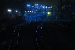 铁路轨道在晚上带领发光和弯曲货物freigh 库存图片