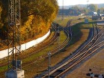 铁路轨道横穿与动臂信号机的在城市 免版税库存图片