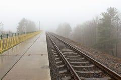 铁路进入薄雾灰色有薄雾的秋天早晨 免版税库存照片
