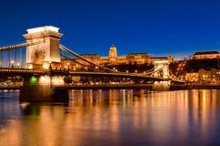 铁锁式桥梁、王宫和多瑙河在布达佩斯在晚上 免版税库存图片