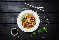 铁锅 乌龙面混乱与鸡和菜的油炸物面条在黑木背景的一块白色板材 筷子和 免版税库存照片