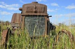 铁锈在长的草的盒拖拉机 免版税库存照片