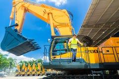铁锹挖掘机建造场所的亚裔工作者 免版税库存图片